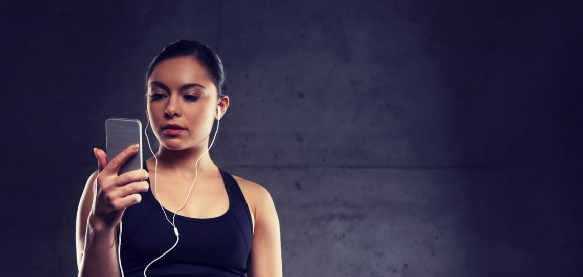 woman with smartphone and earphones in gym P6VKABY